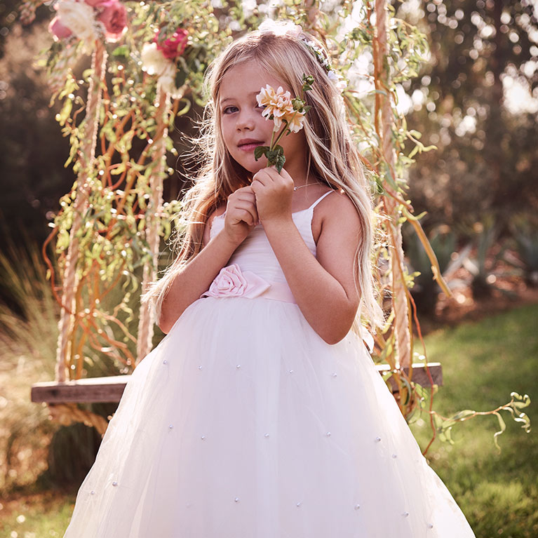 Flower girl in pink dress holding flowers