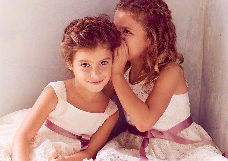 Two flower girls with purple ribbons whispering