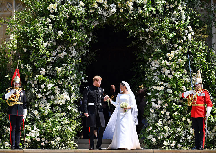 Meghan Markle and Prince Harry standing under an arch of flowers on their wedding day