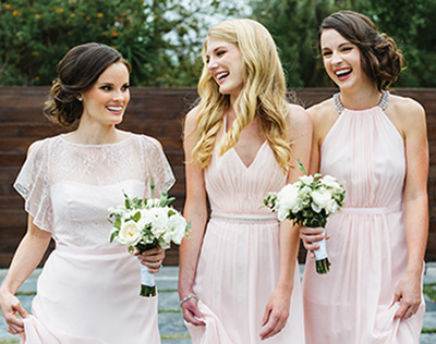 Three bridesmaids wearing blush dresses and laughing