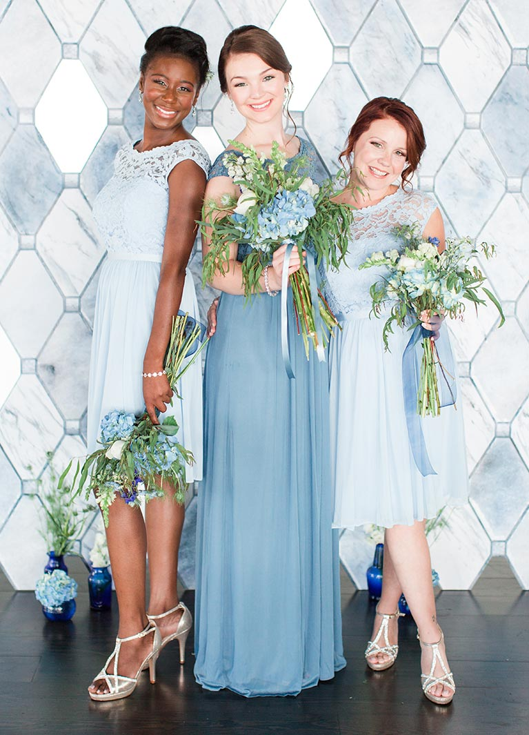 e5a8543a2 Bridesmaid in blue dress with bouquet between two other bridesmaids in  light blue short dresses