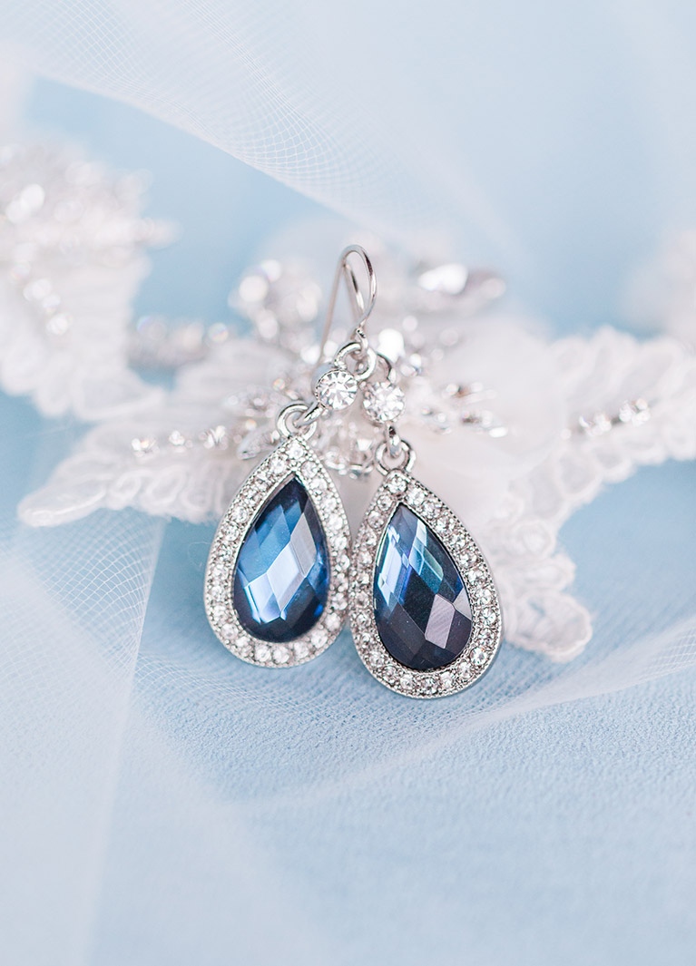 Blue Crystal Halo Teardrop Earrings lay down on veil