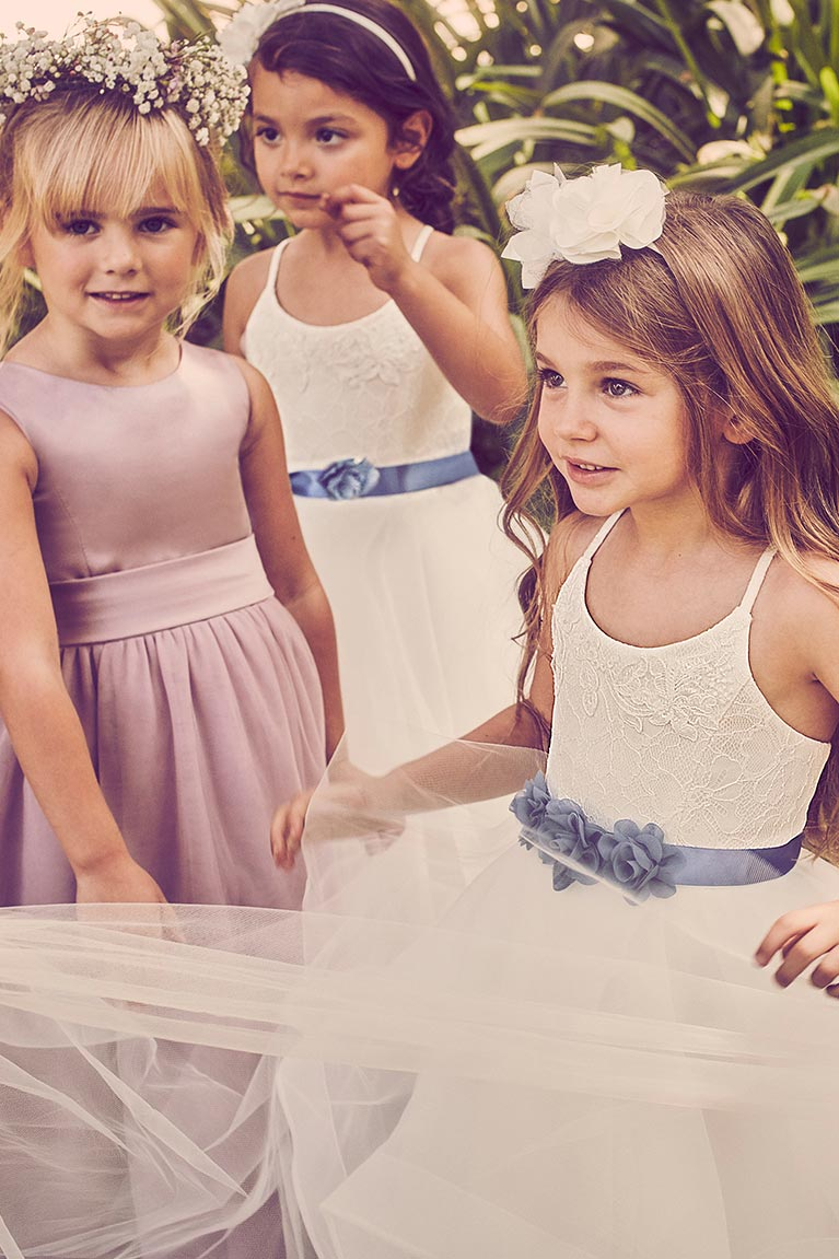 three flower girls in white and purple dresses with floral headpieces