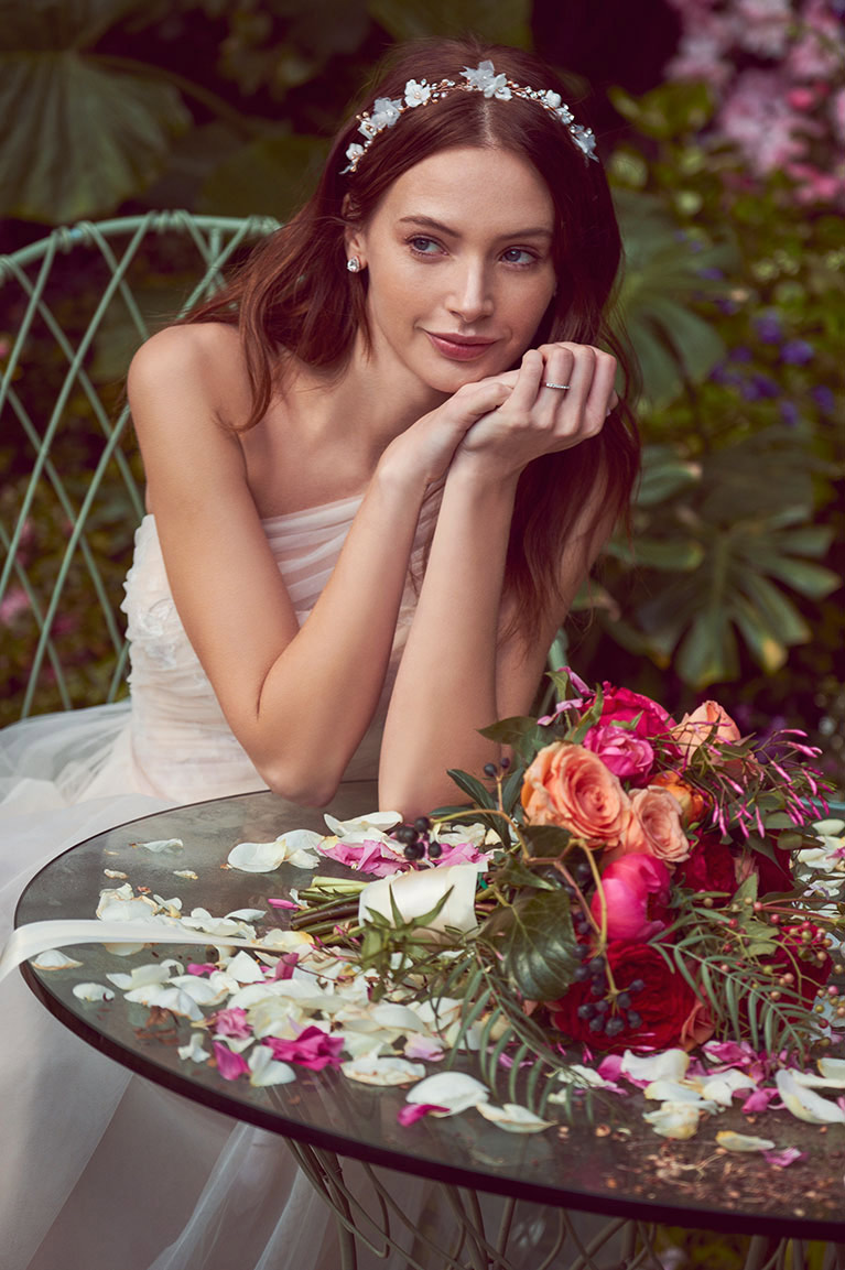 Bride with her elbows rested on a garden table with her bouquet and rose petals