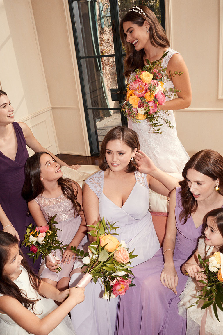 Bride standing behind bridal party smiling down at them