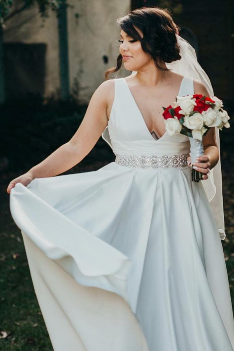 bride in low-cut gown with rhinestone sash