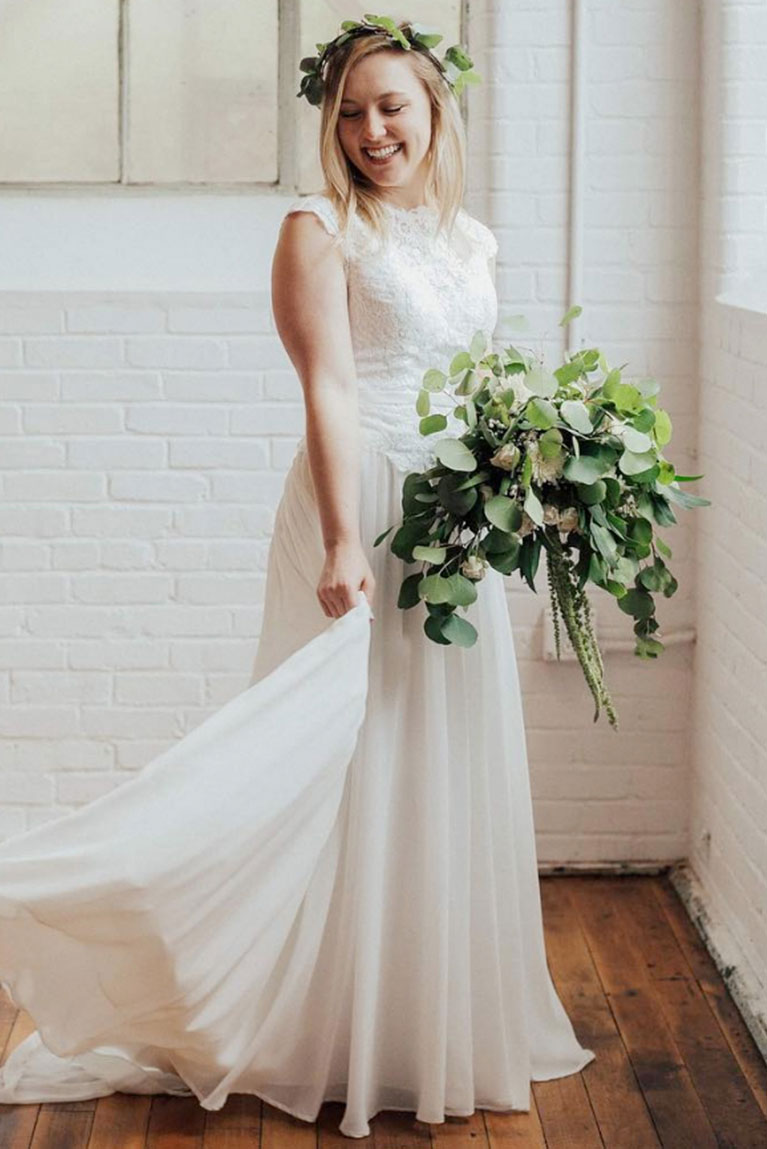 bride carrying green bouquet with matching crown
