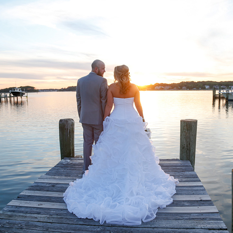 Bride and Groom standing at the end of a dock at sunset