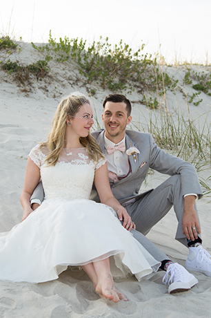 Bride and groom sitting on the beach