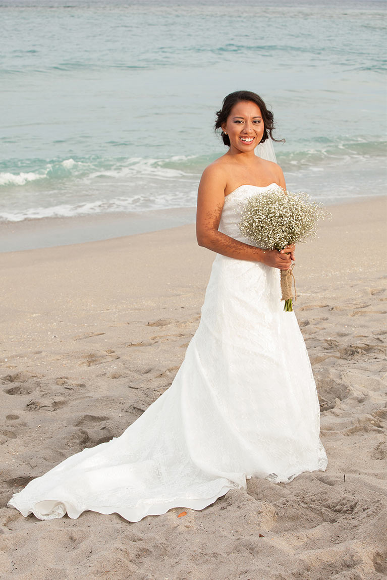 Bride posing with bouquet in front of the ocean