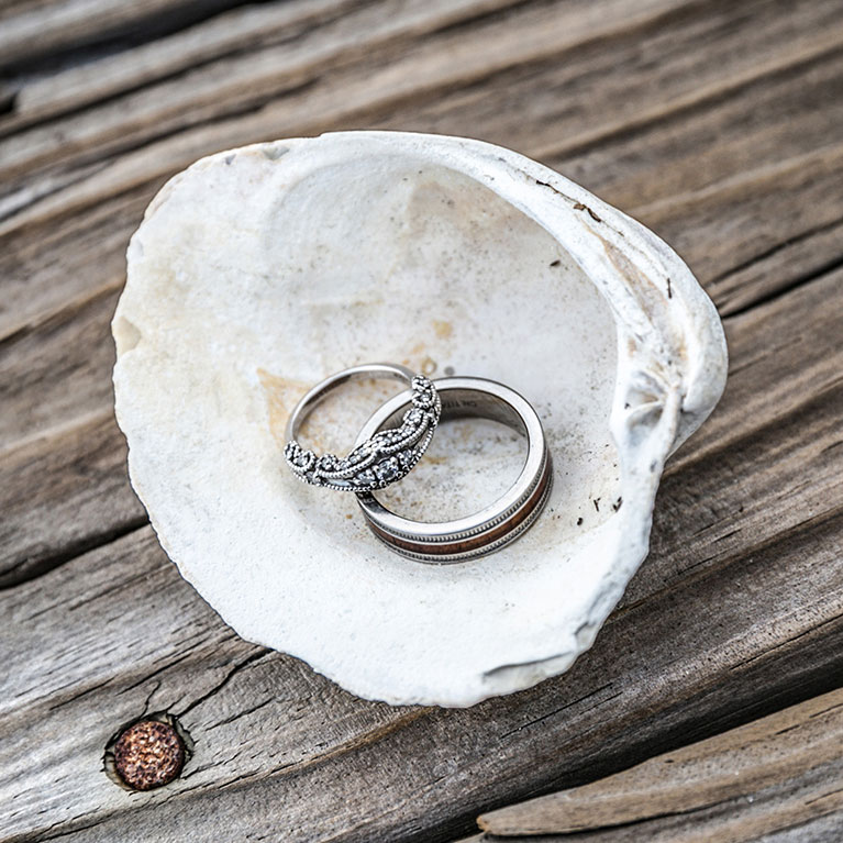 Picture of a seashell with wedding rings placed inside