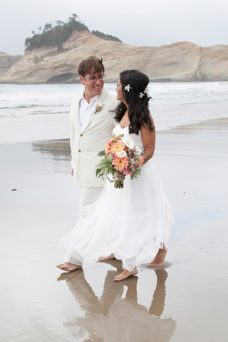 Bride and groom walking on the beach and looking at each other
