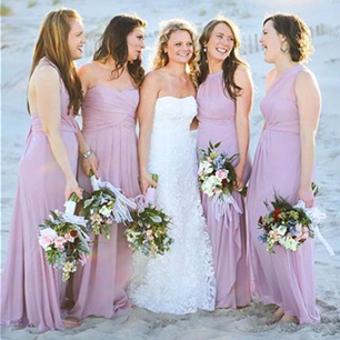 Bride posing with her bridesmaids on the beach
