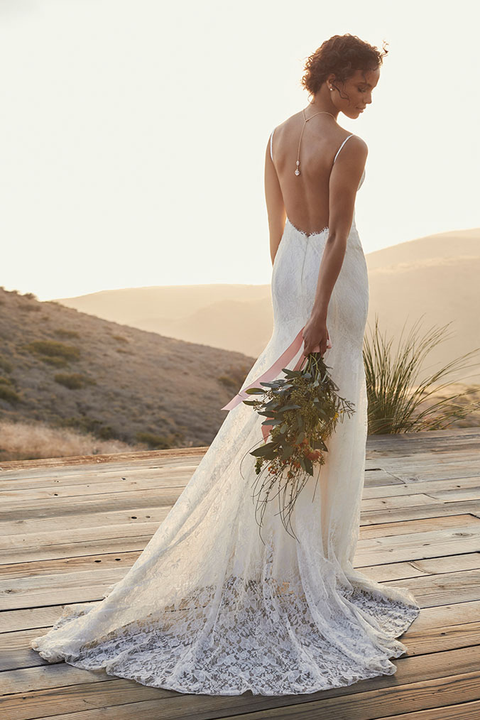 Bride in low open-backed wedding dress, holding bouquet.