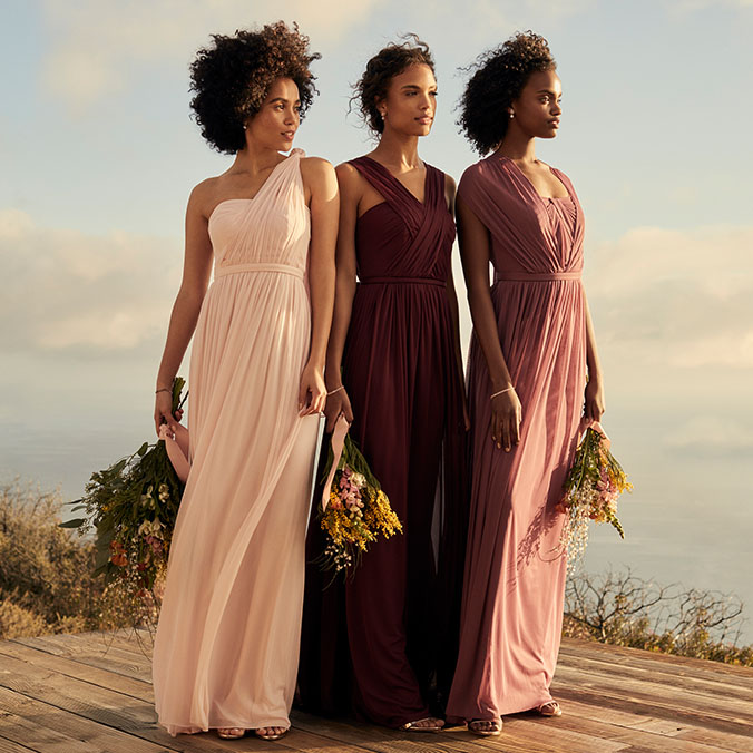 Bridesmaids, in neutral colored dresses, looking out into horizon on seaside cliff.