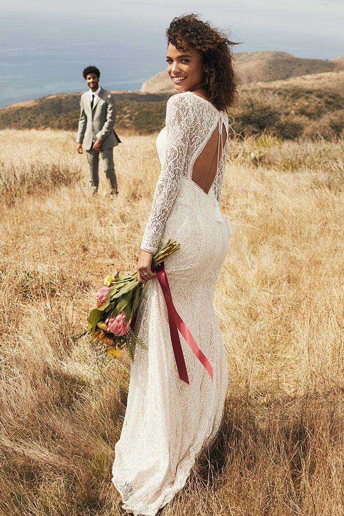 Bride in lace open back dress at beach wedding, holding bouquet.