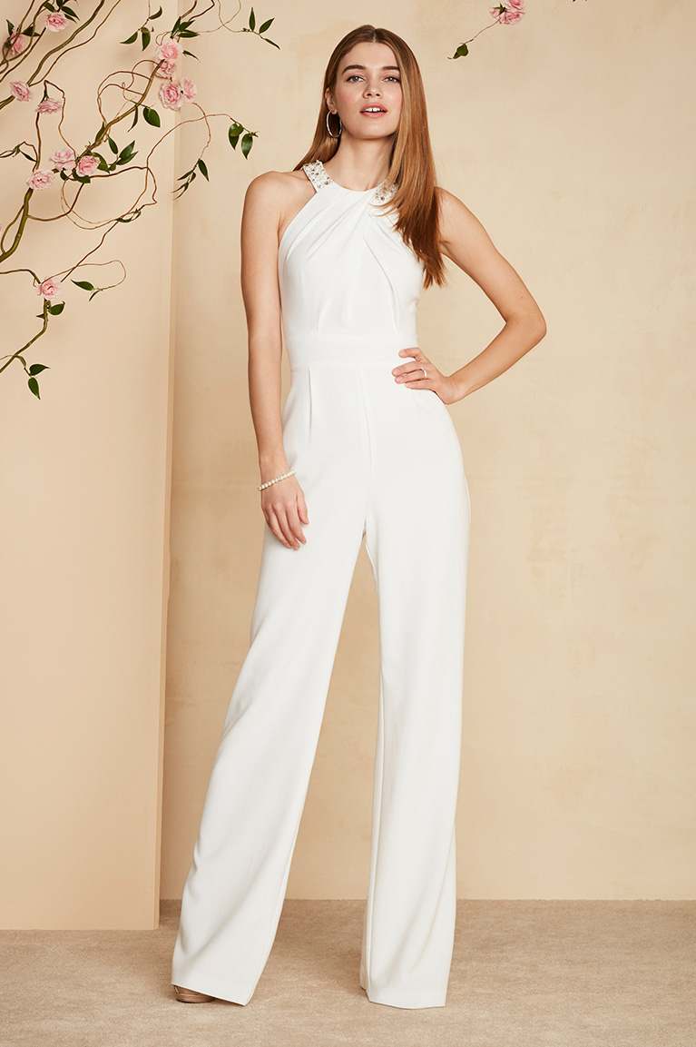 Bride In Halter Jumpsuit Standing With Hand On Hip By Fl Tree Branch