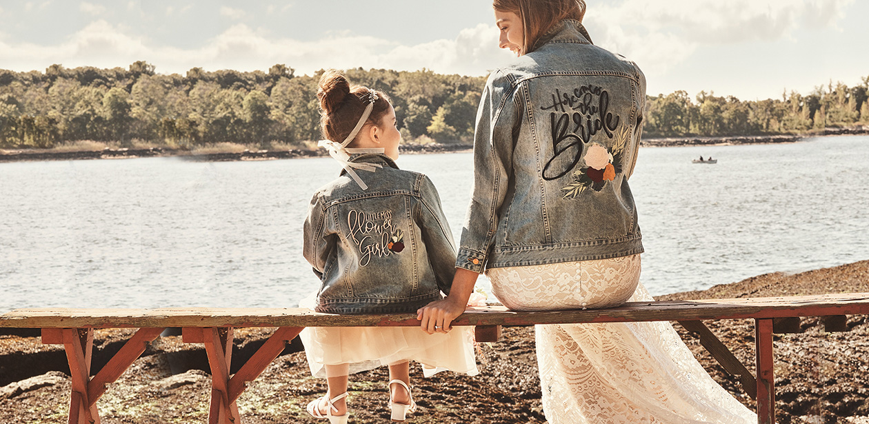 Bride with flower girl wearing matching denim jackets