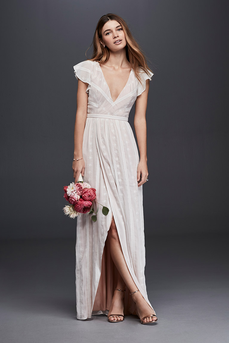 afecf9a3858 Model posing in wedding gown with bouquet