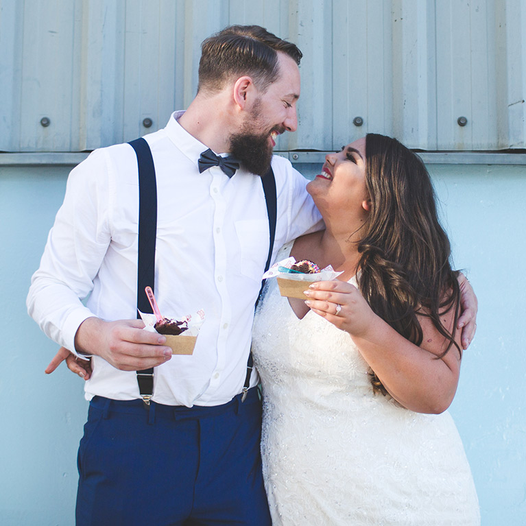 Image of bride and groom smiling at each other while eating ice cream