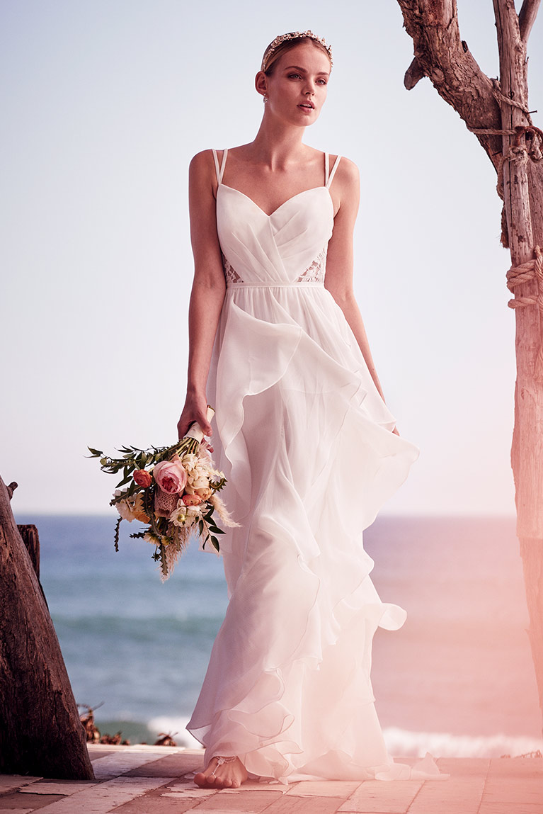 78959bd2505 Image of bride wearing a flowy wedding gwon near the beach