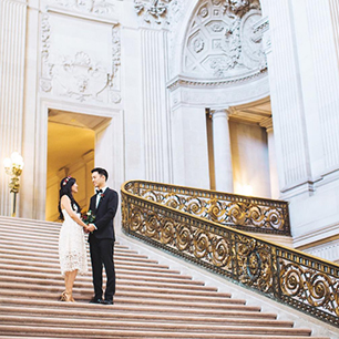 Bride in short wedding dress & groom standing on grand stairwell