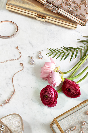 Flowers and jewelry spread across marble tabletop