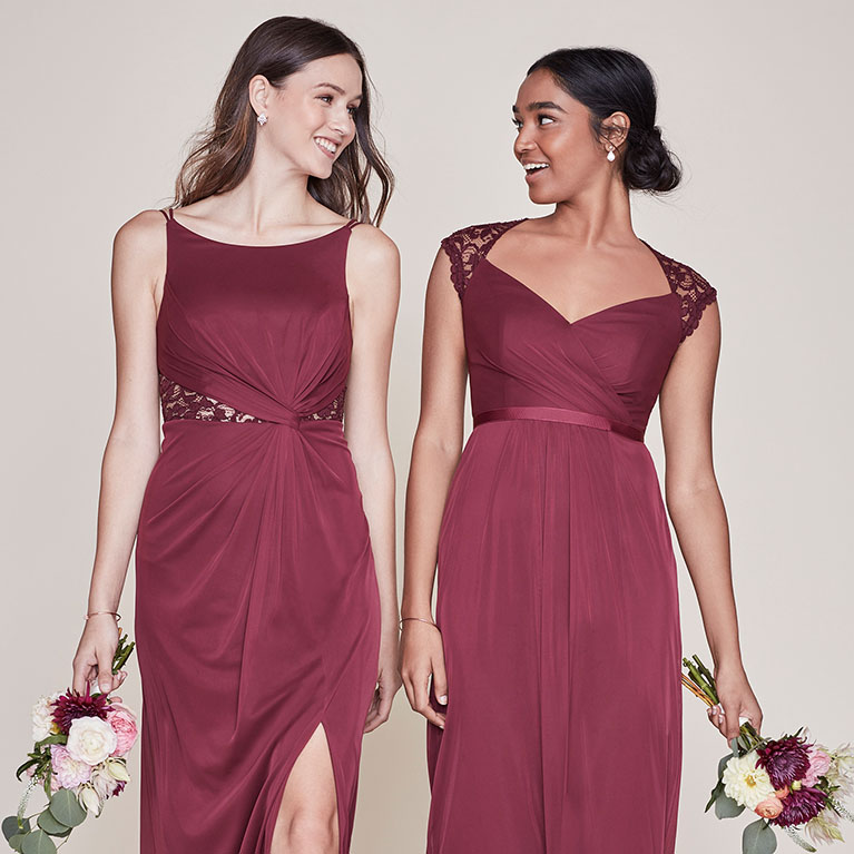 Two bridesmaids in wine colored dresses smiling at each other