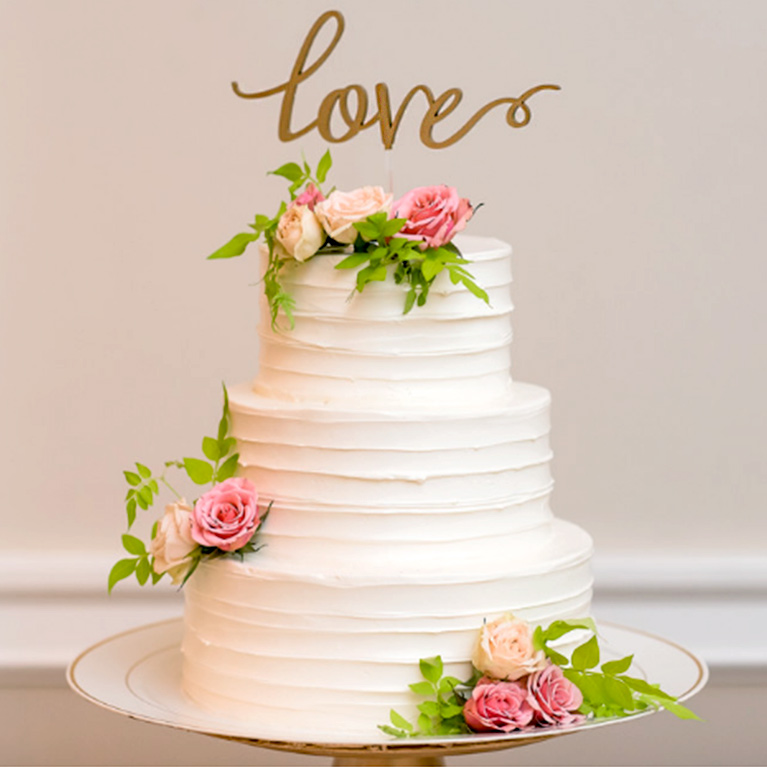 White cake with pink flower and gold cursive Love cake topper
