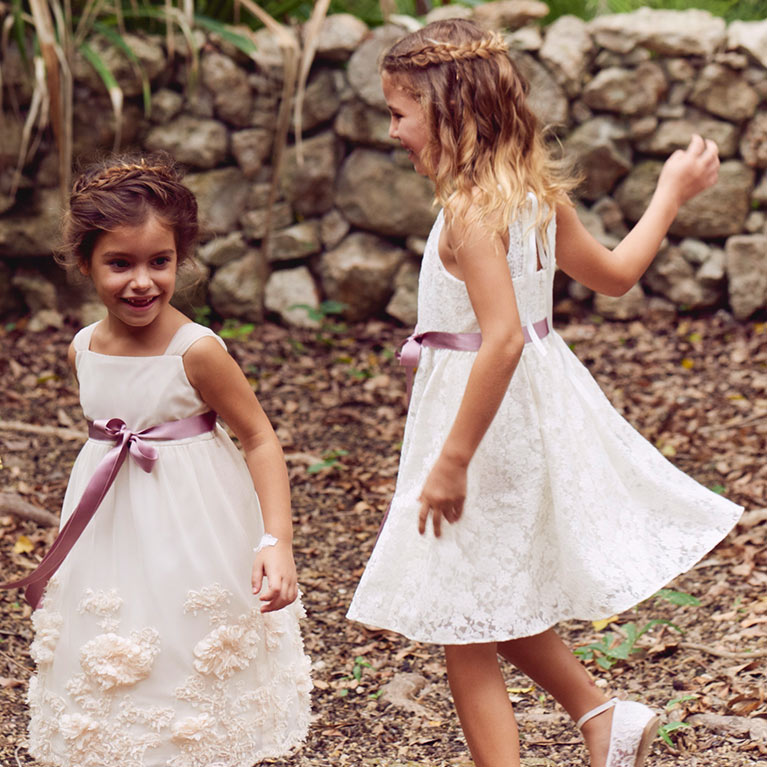 Flower girls playing by stone wall