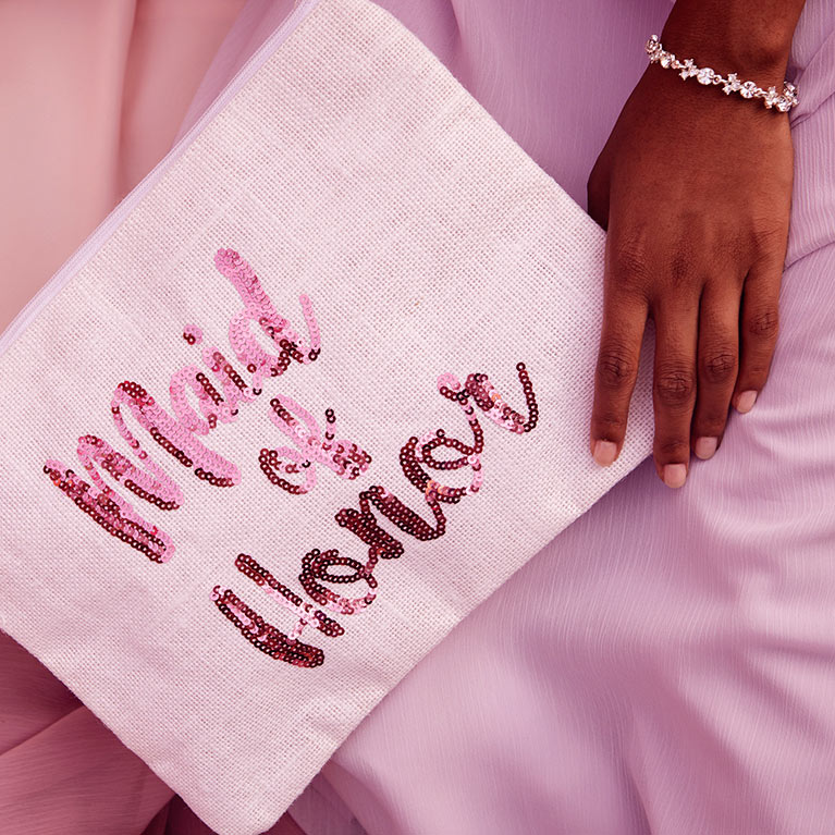 Bridesmaid holding sequin Maid of Honor bag