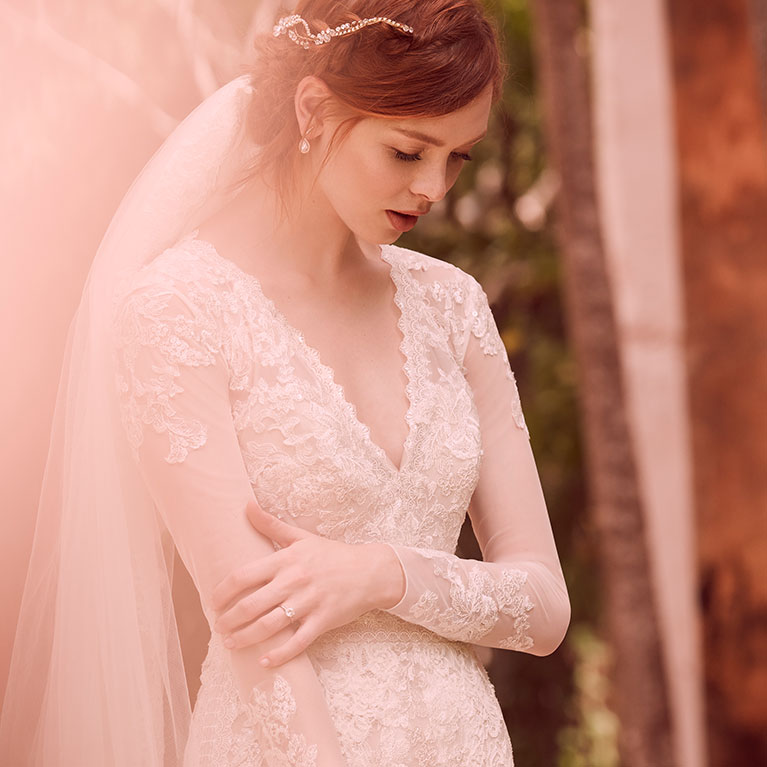 Bride in lace long sleeve wedding gown gazing down