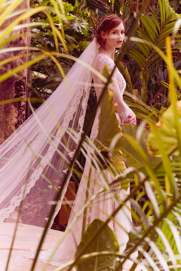 Bride with cathedral viel standing by palm leaves