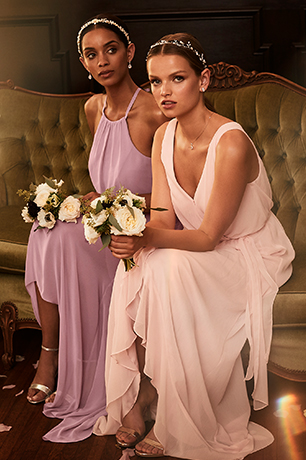 Two bridesmaids in mismatched pink dresses.