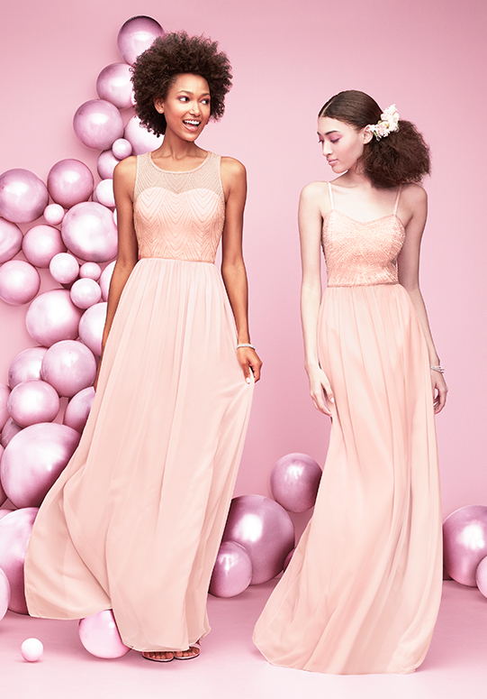 Two women in pink, embellished bridesmaid dresses