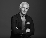 Black and white photo of Joseph Abboud in suit with arms crossed