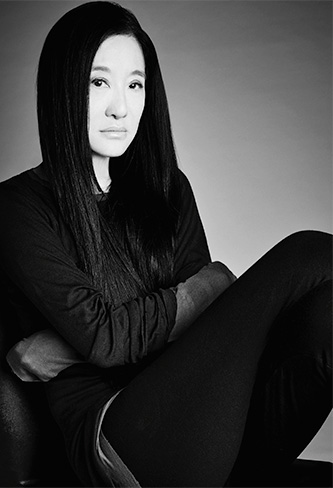 Black and white photo of Vera Wang dressed in all black sitting with arms crossed