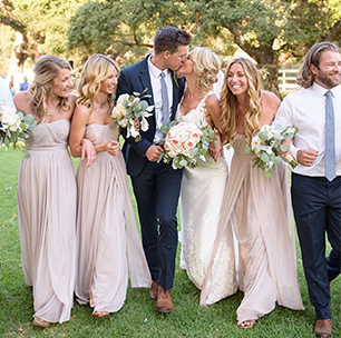 Bridal Party Laughing as Bride and Groom Kiss