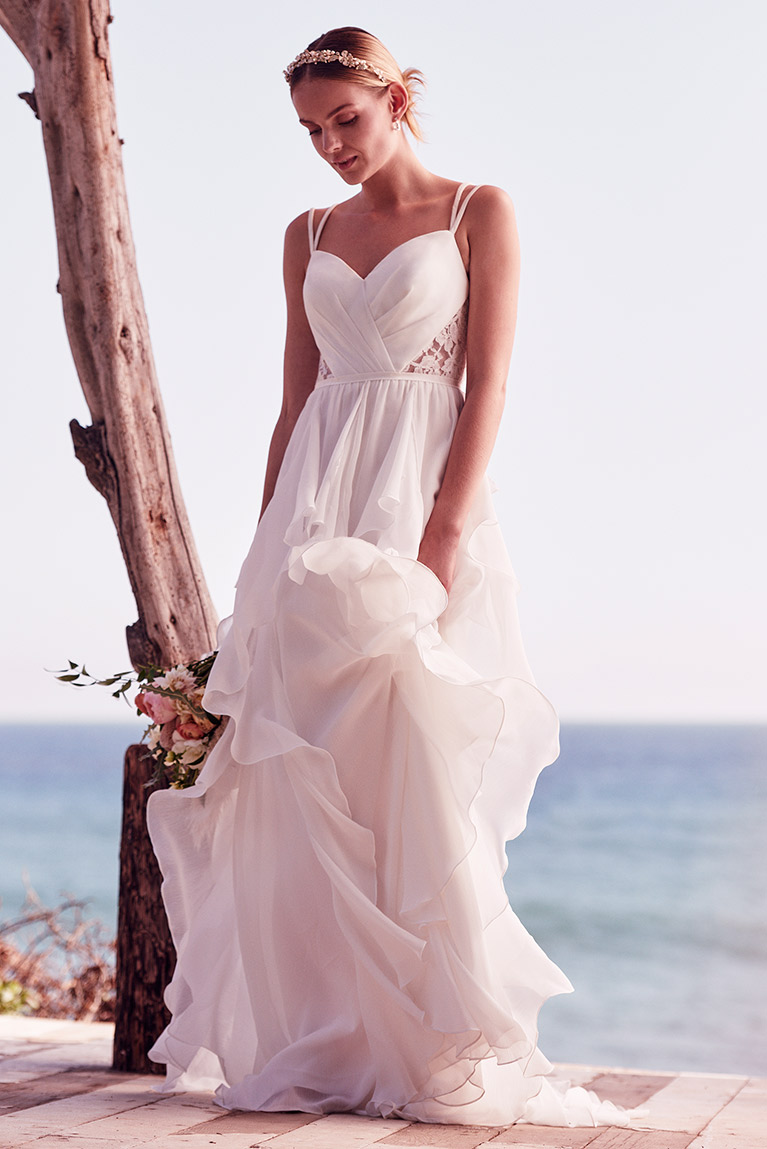 Bride standing on dock in long wedding gown