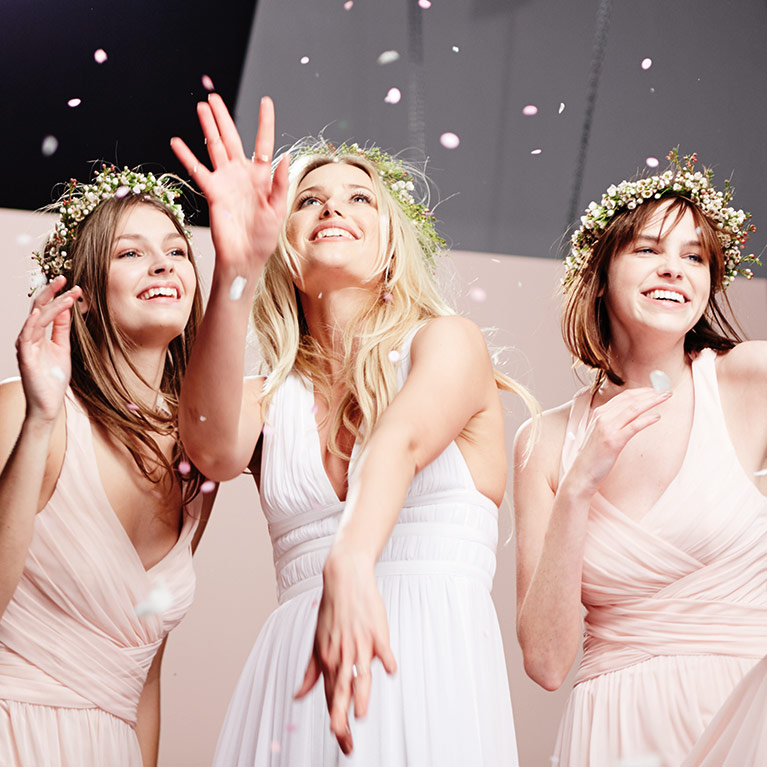 Bride and two bridesmaids wearing bohemian flower crowns