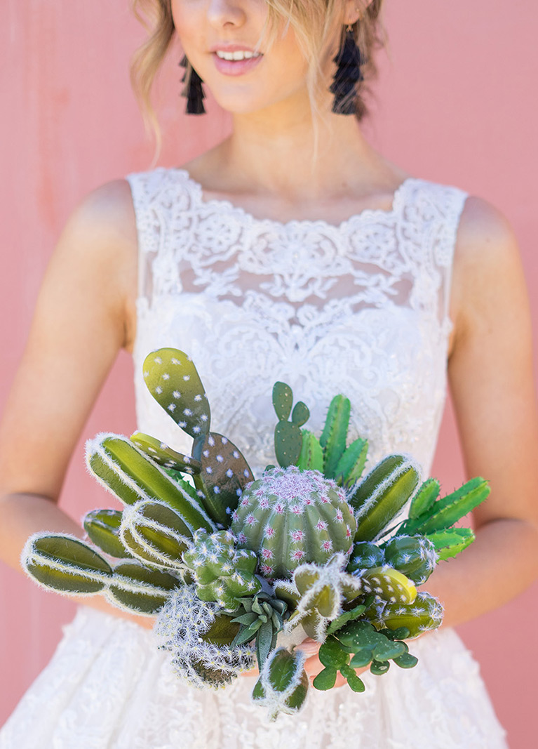 Bride carrying cactus and succulent bouquet.