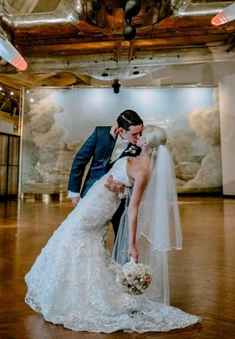 Romantic bride and groom kissing in museum