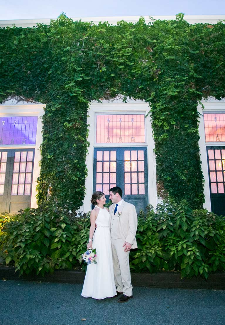 Bride and groom standing by vine covered building