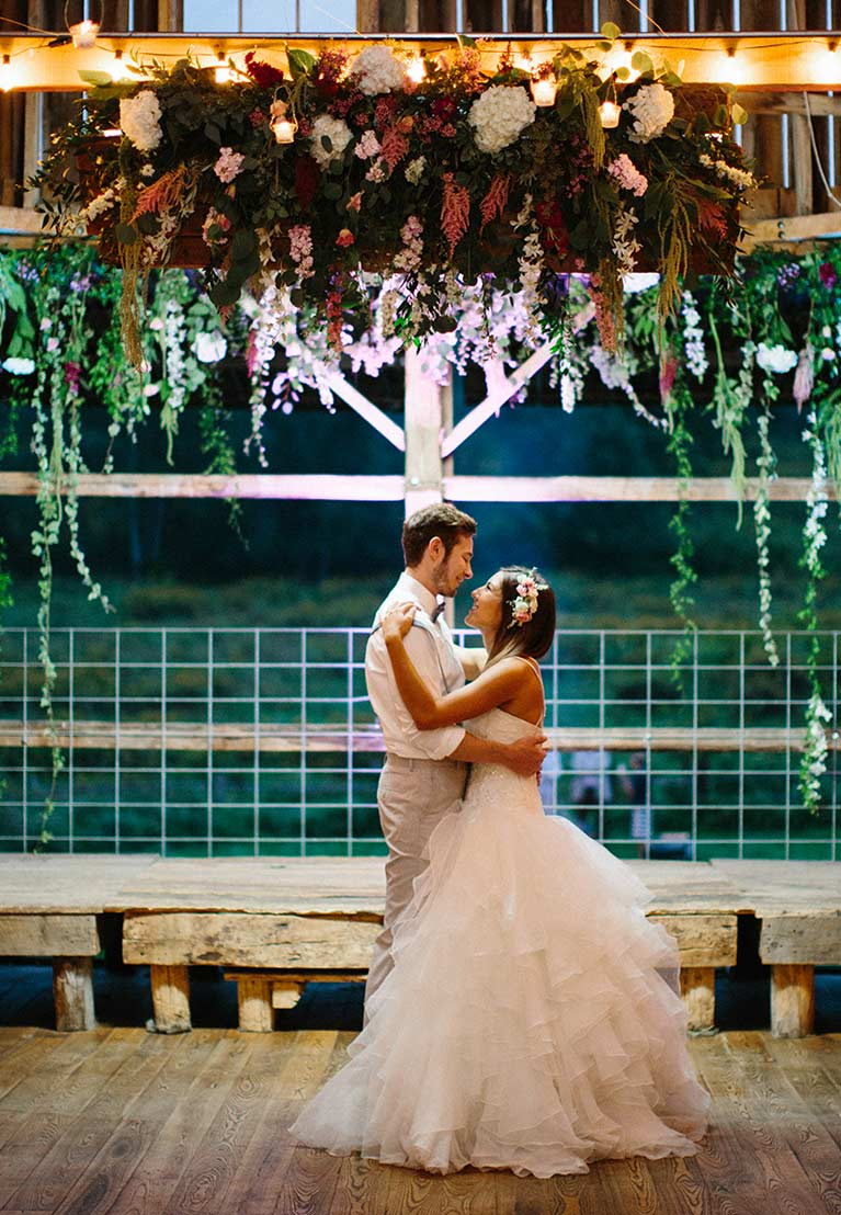 Bride and groom dancing under hanging flower arch