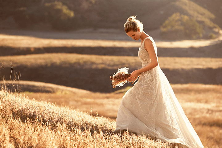 Woman walking up a hill in a field wearing a white gown and holding flowers as the sun sets