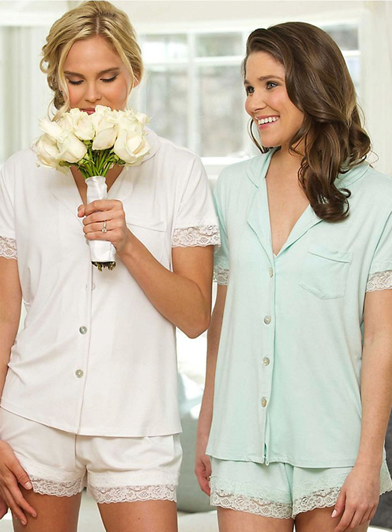 Bride and bridesmaid wearing mismatched pajama sets.