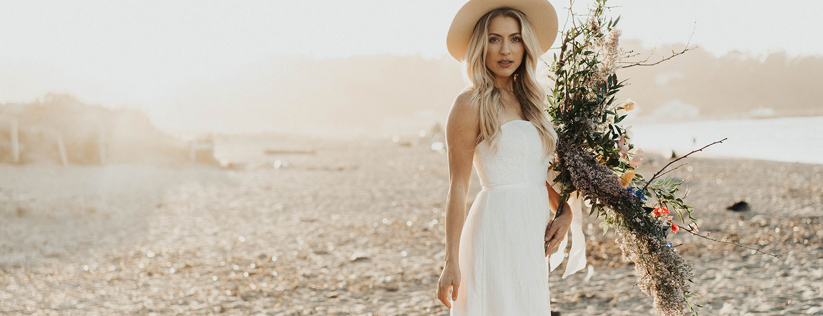 Bride holding bouquet in casual wedding dress, on beach.