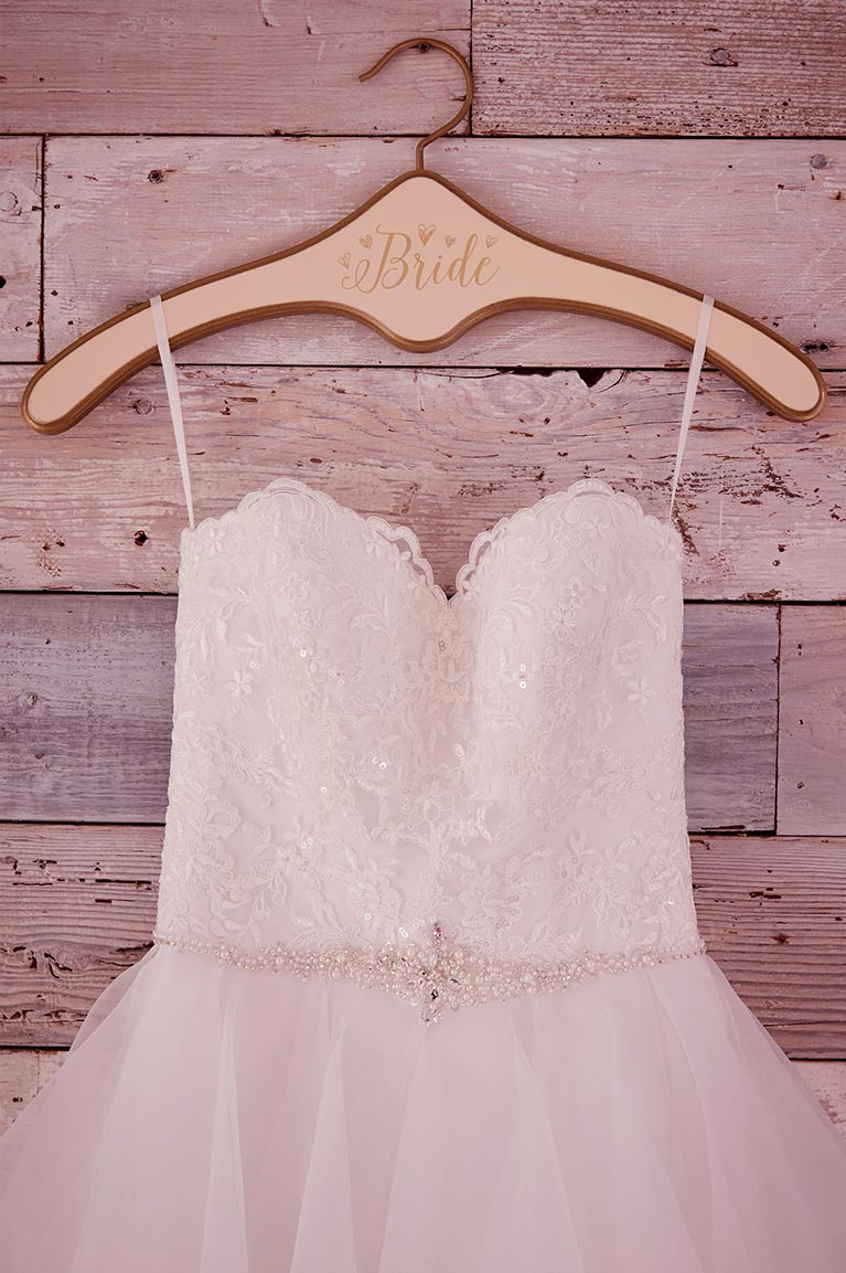 Strapless dress with sparkle bodice and tulle skirt hanging on Bride hanger