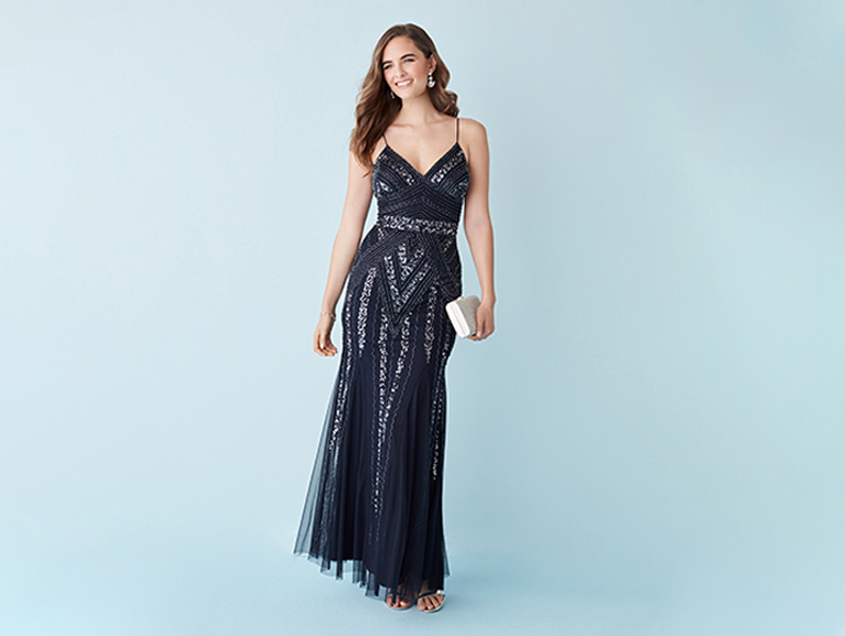 6bedebd171b9 Woman posing in a navy blue sparkly dress holding a handbag to her side.