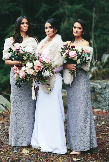 Bridesmaids and bride standing outside with fur wraps and large bouquets
